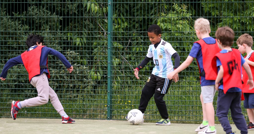 child playing football with his friends