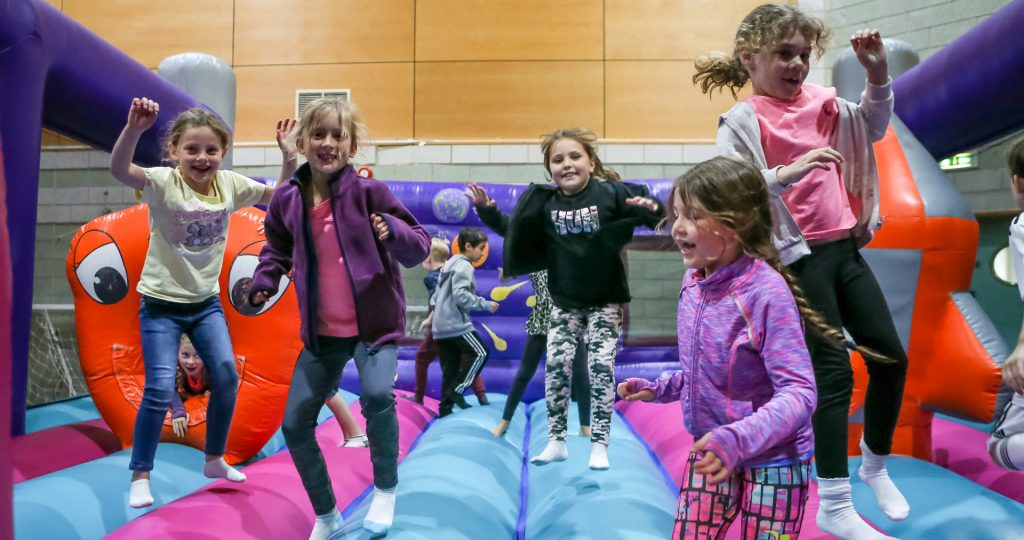 PlaySport - children having fun on a bouncy castle during the school holiday