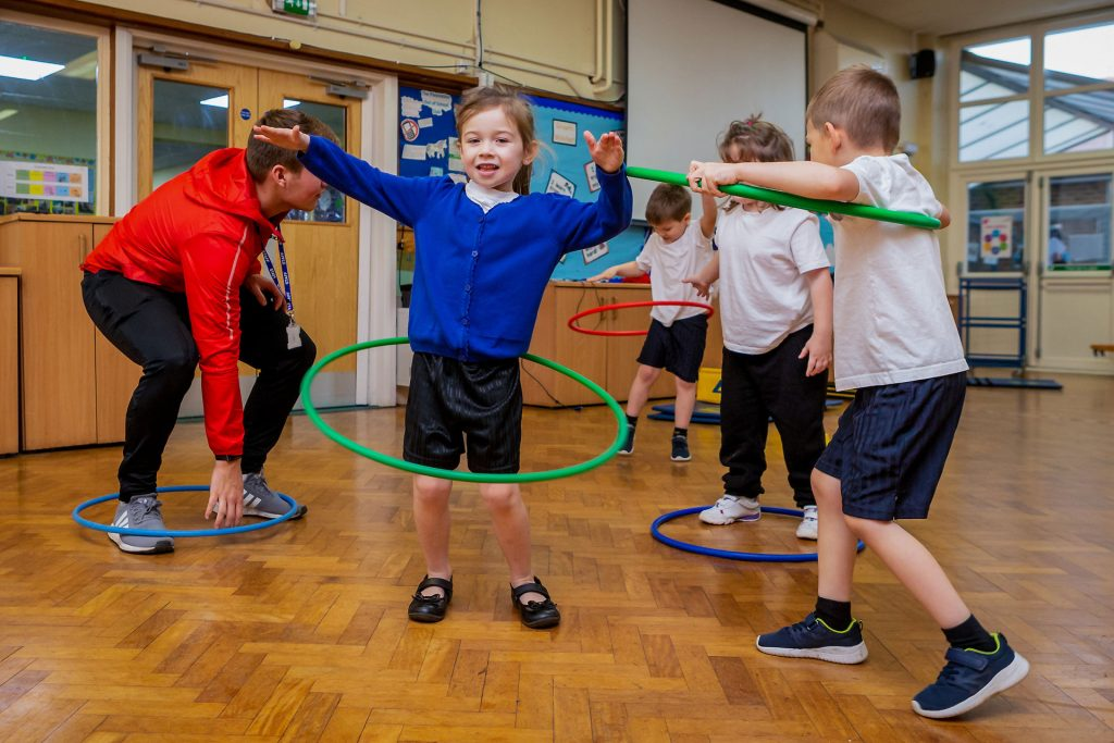 PlaySport - children having fun with hula hoops during a primary school pe lesson